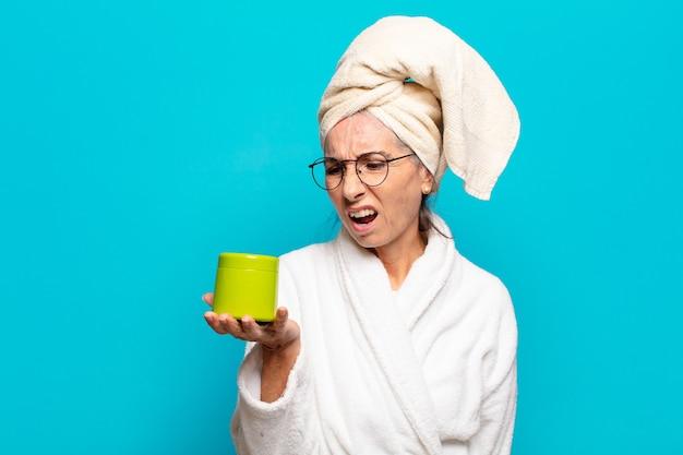 Starszy ładna kobieta po prysznicu na sobie szlafrok. koncepcja produktów do czyszczenia twarzy lub produktów pod prysznic