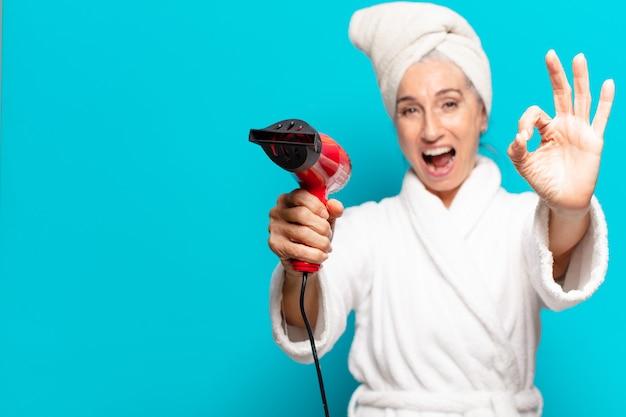 Starszy ładna kobieta po prysznicu na sobie szlafrok. koncepcja suszarki do włosów