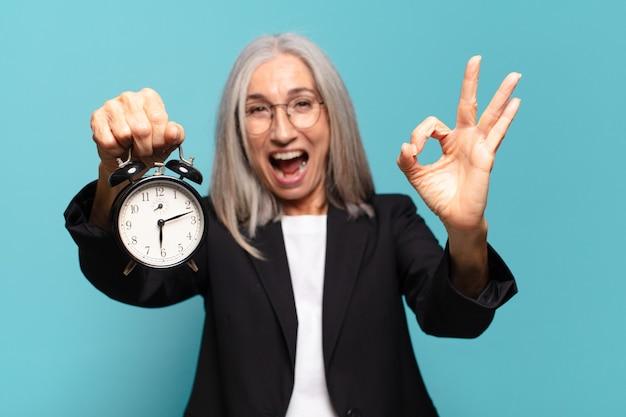 Starszy ładny bizneswoman z budzikiem. koncepcja czasu