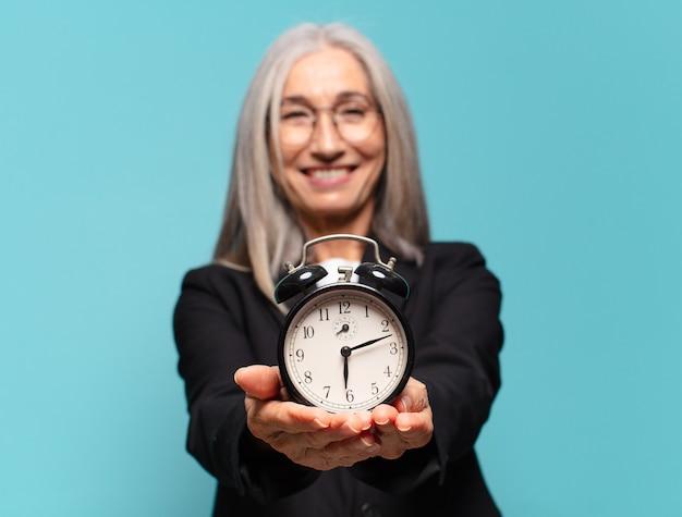 Starszy ładny bizneswoman z budzikiem. pojęcie czasu