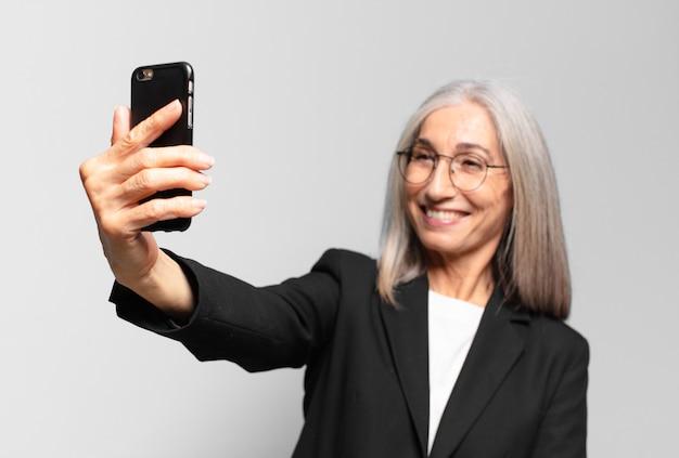 Starszy ładny bizneswoman z mądrze telefonem.