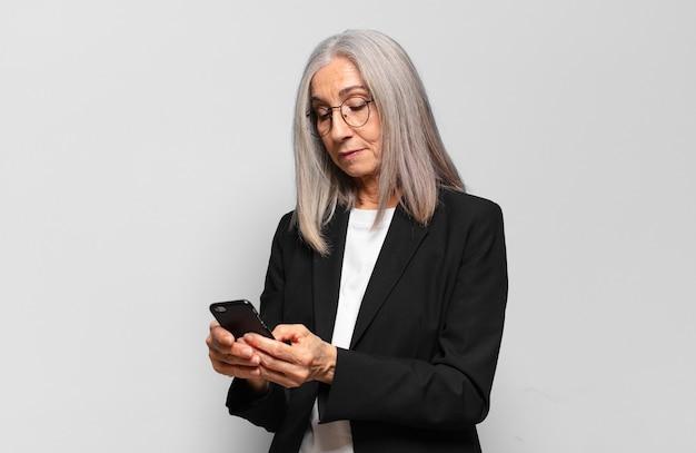 Starszy ładny bizneswoman z mądrze telefonem