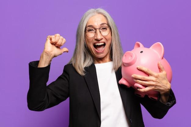 Starszy ładny bizneswoman z piggy bank