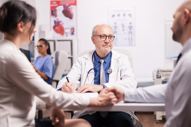 Starszy lekarz daje złe wieści młodej parze podczas badania lekarskiego w gabinecie szpitalnym. mąż i żona trzymając się za ręce. pielęgniarka patrząc na prześwietlenie pacjenta.