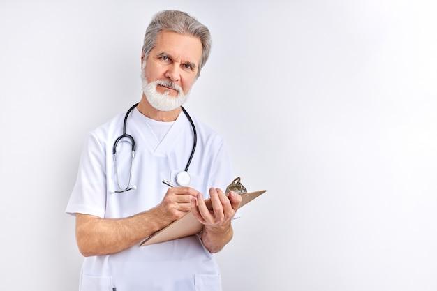 Starszy lekarz mężczyzna robi notatki w tablecie na sobie stetoskop na białym tle na białym studio