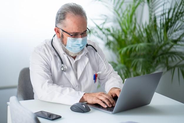Starszy lekarz pracujący z laptopem w swoim gabinecie z założoną maską na twarz