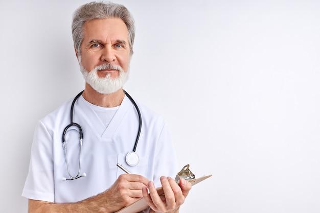 Starszy lekarz przeprowadzający wywiad medyczny pacjenta, rób notatki, pisz w tablecie, używaj stetoskopu