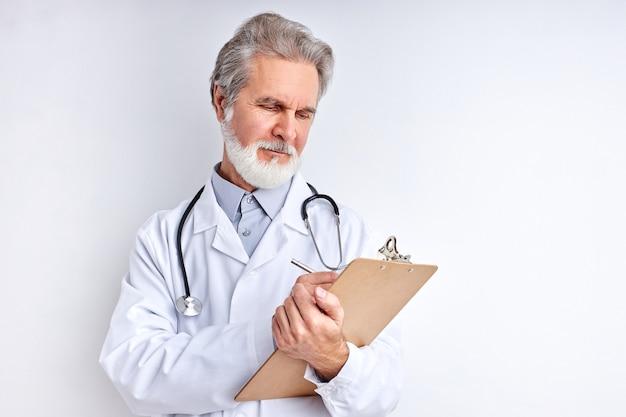 Starszy lekarz przeprowadzający wywiad medyczny pacjenta, robić notatki, pisać w tablecie