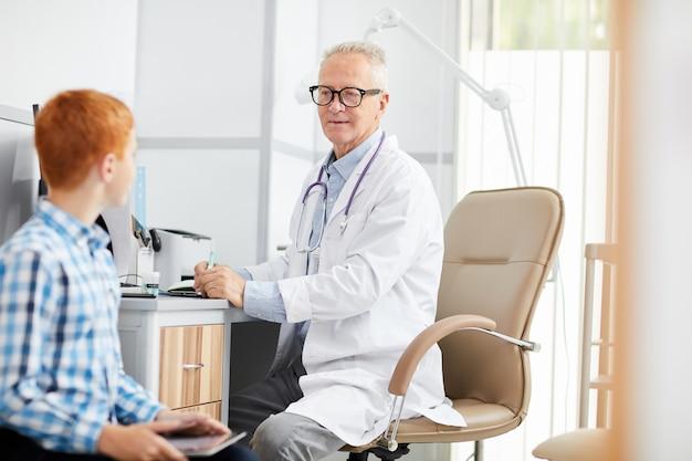 Starszy lekarz rozmawia z nastoletnim chłopcem