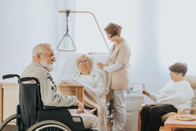 Starszy lekarz w beżowym mundurze rozmawia ze starszym pacjentem podczas spaceru po szpitalu