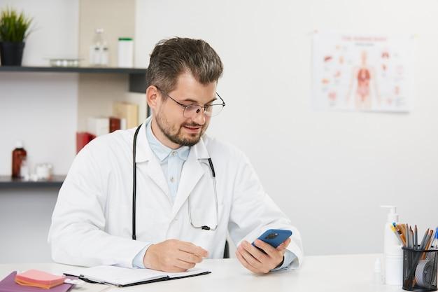 Starszy lekarz w białej sukni za pomocą smartfona w pracy, brodaty mężczyzna pediatra w białym mundurze medycznym i okularach siedzi w szafce medycznej ze stetoskopem i trzyma telefon