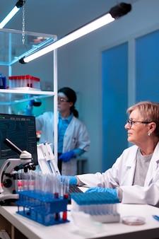 Starszy lekarz w białym fartuchu pracuje na komputerze, szczepionce, chemii, probówce, medycynie