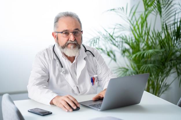Starszy lekarz z laptopem w swoim gabinecie