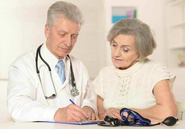 Starszy lekarz z pacjentem na białym tle