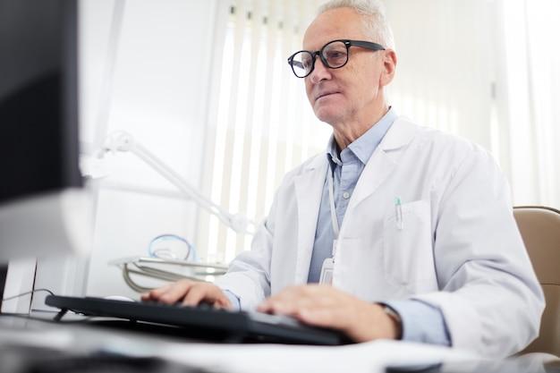 Starszy lekarz za pomocą komputera