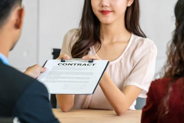 Starszy menedżer ds. azji przesyła dokument umowy do absolwentki młodej azjatki