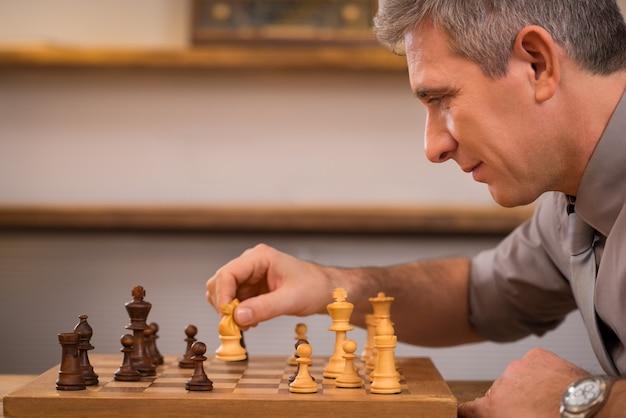 Starszy menedżer gra w szachy w biurze. dojrzały biznesmen myśli nad następnym ruchem w szachy. przywództwo cieszy się następnym ruchem w szachach. koncepcja strategii i zarządzania.