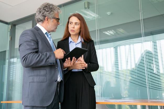 Starszy menedżer rozmawia z pracownikiem, trzymając tablet i stojąc w sali konferencyjnej