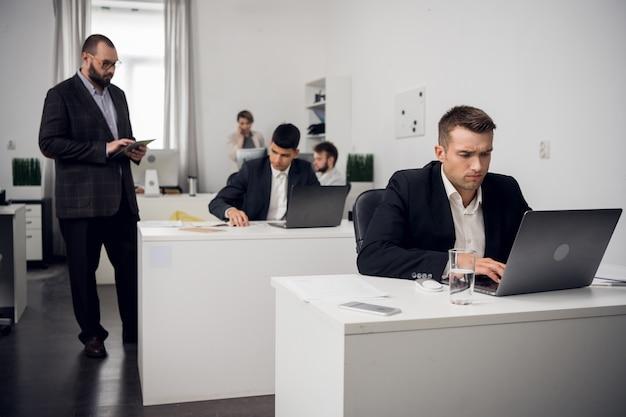 Starszy menedżer sprawdza jakość zadań wykonywanych przez jego młodszych pracowników siedząc przy komputerze w biurze firmy finansowej.