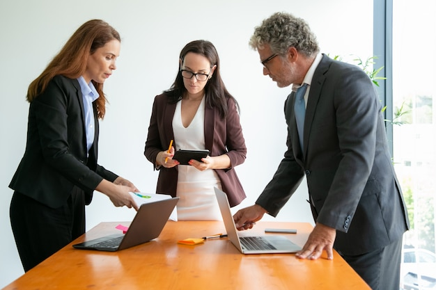 Starszy menedżer w okularach rozmawia z kobietami biznesu i korzysta z laptopa