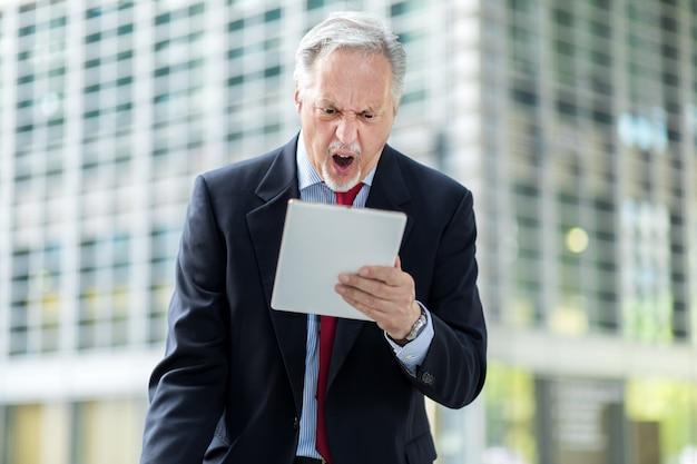 Starszy menedżer wygląda zirytowany, ponieważ czyta złe wieści na swoim tablecie