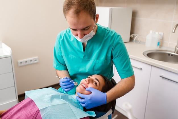 Starszy męski dentysta opowiada w żeńskim pacjencie i przygotowywa dla leczenia w stomatologicznym biurze.