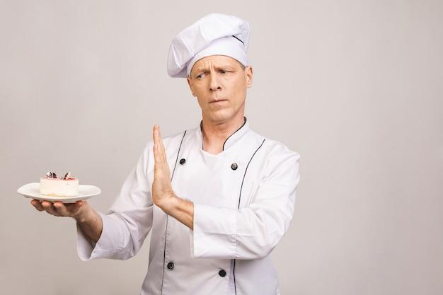 Starszy męski szefa kuchni kucharz lub piekarza mężczyzna w bielu munduru pozować odizolowywam na biel ścianie. gotowanie koncepcja żywności. pokazuje gest zatrzymania na talerz z ciastem