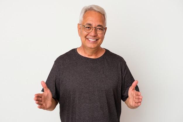 Starszy mężczyzna amerykański na białym tle trzymając coś obiema rękami, prezentacja produktu.