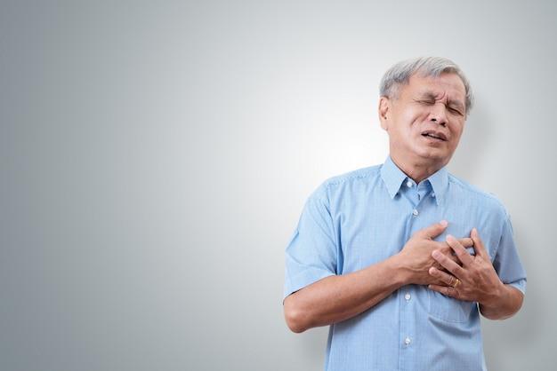 Starszy mężczyzna azji, trzymając się za klatkę piersiową i powodując ból w klatce piersiowej od ataku serca.