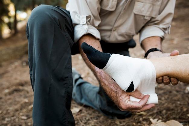 Starszy mężczyzna bandażuje żonę