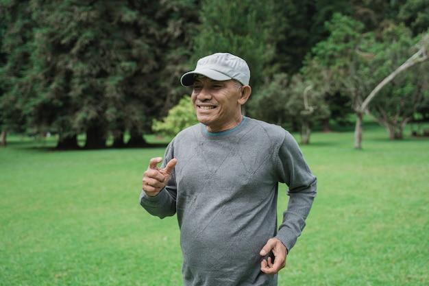 Starszy mężczyzna bieg w ogródzie