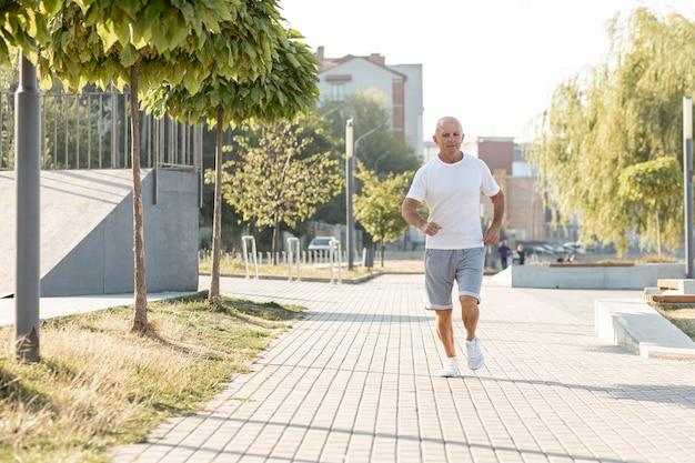 Starszy mężczyzna biegnący na chodniku