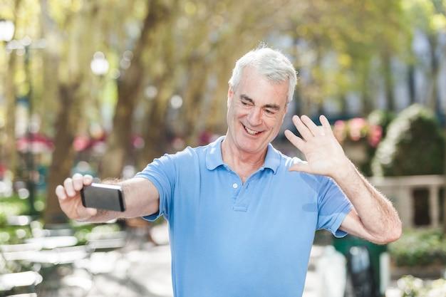 Starszy mężczyzna bierze selfie przy parkiem
