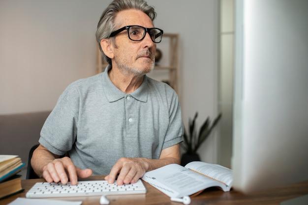 Starszy mężczyzna biorący lekcję online na swoim komputerze