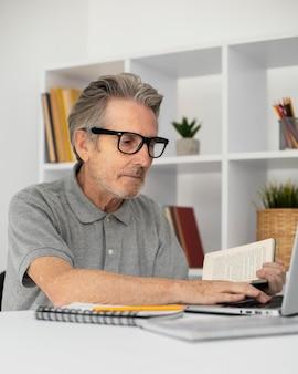 Starszy mężczyzna biorący lekcję online na swoim laptopie