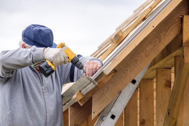 Starszy mężczyzna budowniczy śrubokrętem przykręcenie blachodachówki do dachu