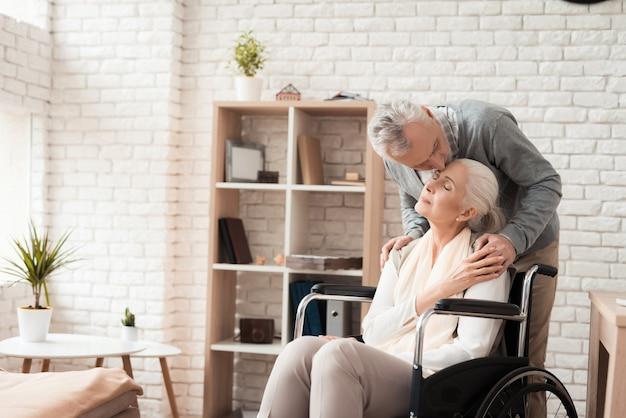 Starszy mężczyzna całuje w czoło dojrzałej kobiety na wózku inwalidzkim.