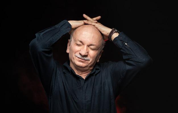 Starszy mężczyzna cierpi na ból głowy.