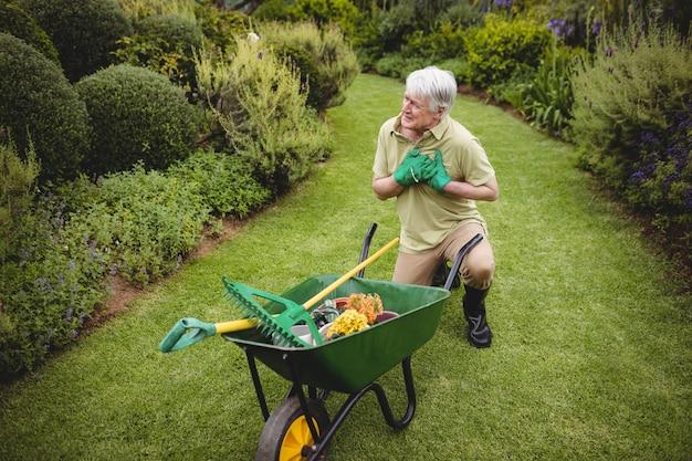 Starszy mężczyzna cierpi na ból podczas ogrodnictwa
