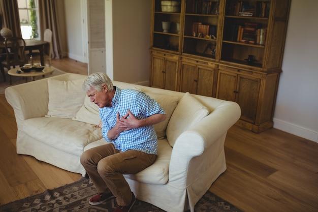 Starszy mężczyzna cierpi na ból w klatce piersiowej w salonie
