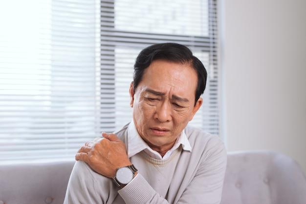 Starszy mężczyzna cierpiący na ból barku siedzący na kanapie w salonie