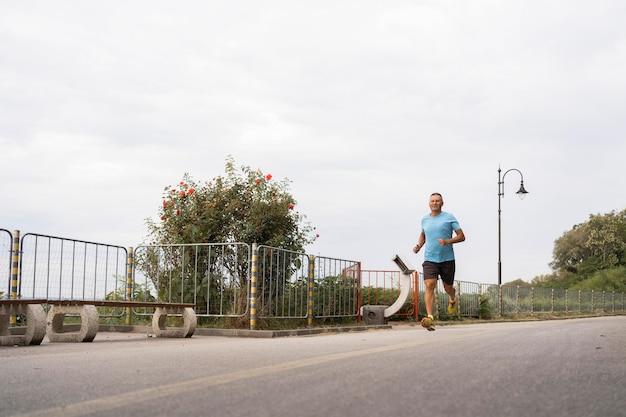 Starszy mężczyzna ćwiczy jogging na świeżym powietrzu przez park