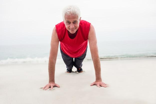 Starszy mężczyzna ćwiczy na plaży