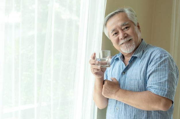Starszy mężczyzna czuje się szczęśliwy picia świeżej wody rano, ciesząc się czas w swoim domu