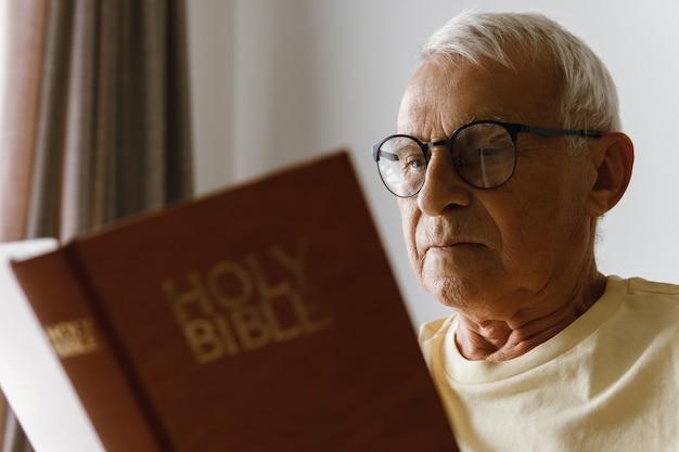 Starszy mężczyzna czyta biblię w domu
