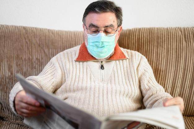 Starszy mężczyzna czyta gazetę podczas kwarantanny epidemicznej koronawirusa.