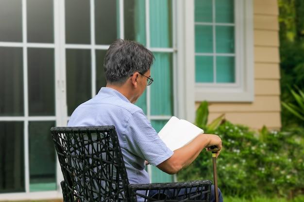 Starszy mężczyzna czyta i relaksuje się na podwórku