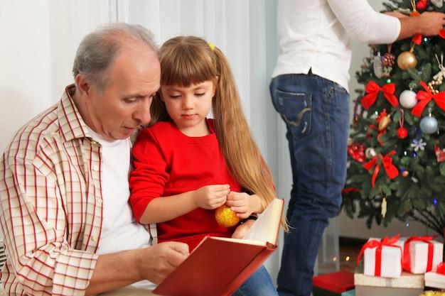 Starszy mężczyzna czyta książkę z wnuczką w salonie udekorowanym na boże narodzenie