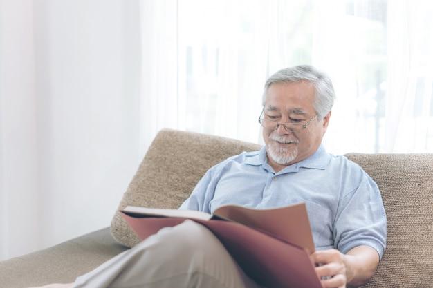 Starszy mężczyzna czytanie powieści książki, uśmiechnięty czuć się szczęśliwy na kanapie w domu
