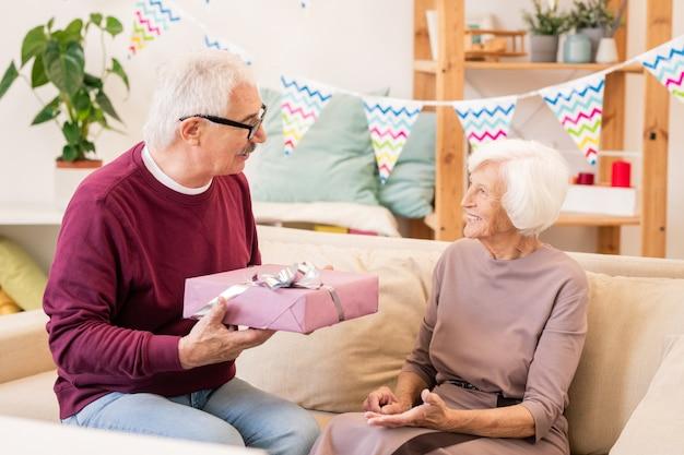 Starszy mężczyzna daje żonie zapakowany prezent na imprezie domowej i życzy jej wszystkiego najlepszego